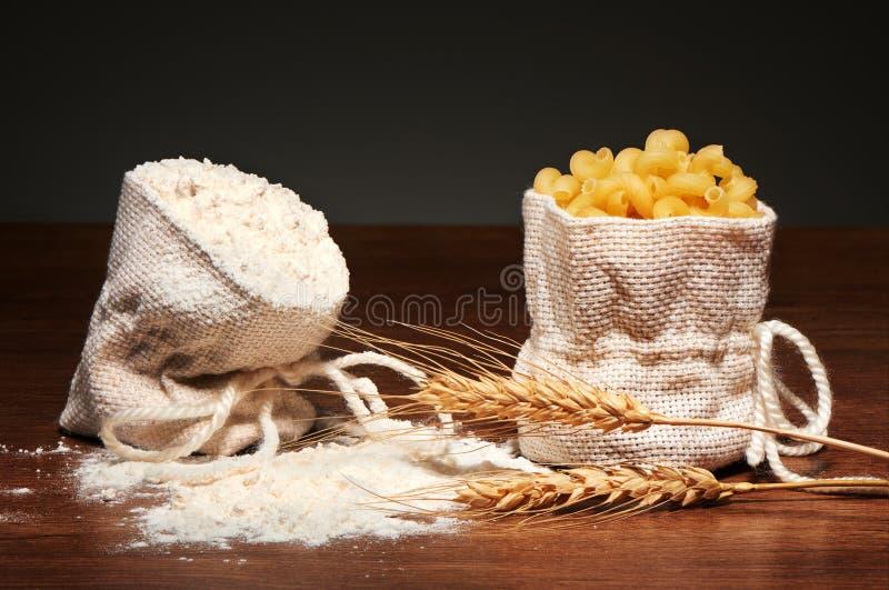 Säckvävpåsar av mjöl och torr cavatappipasta, veteöron royaltyfri bild