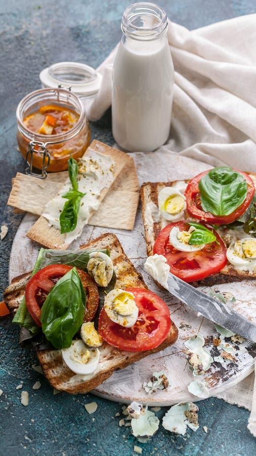 Sädes- rostade bröd med ost, nya tomater, basilikasidor och vaktelägg smakligt och sunt frukostbegrepp Skjuten lodlinje royaltyfria bilder