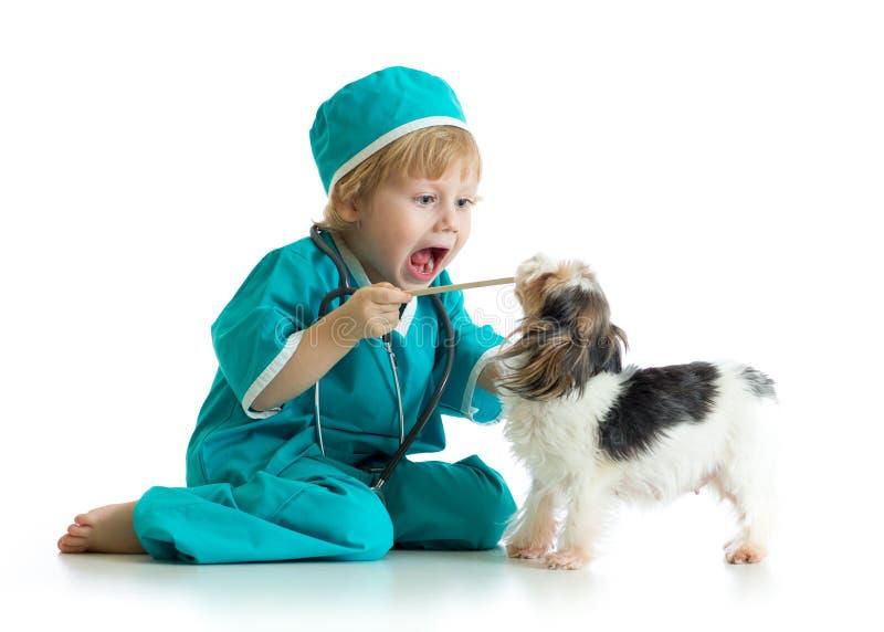 Säg aaah - barn weared doktorskläder som spelar veterinären royaltyfri foto