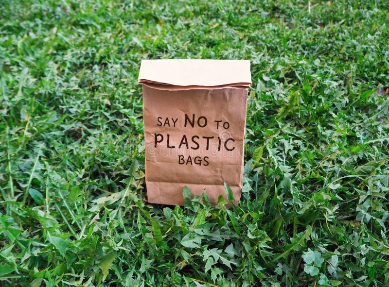 Säg inte till den ekologiska shoppa påsen för plastpåsar på det gröna gräset royaltyfri bild
