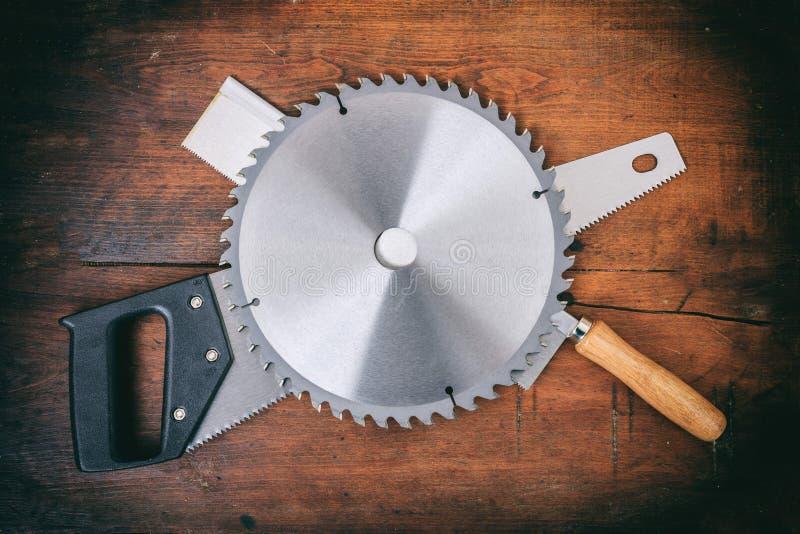 Sägeblatt und Handsägen auf hölzernem Hintergrund stockfoto