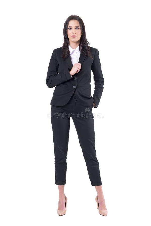 Säker affärskvinna i den svarta eleganta dräktinnehavkragen som poserar och ser kameran fotografering för bildbyråer