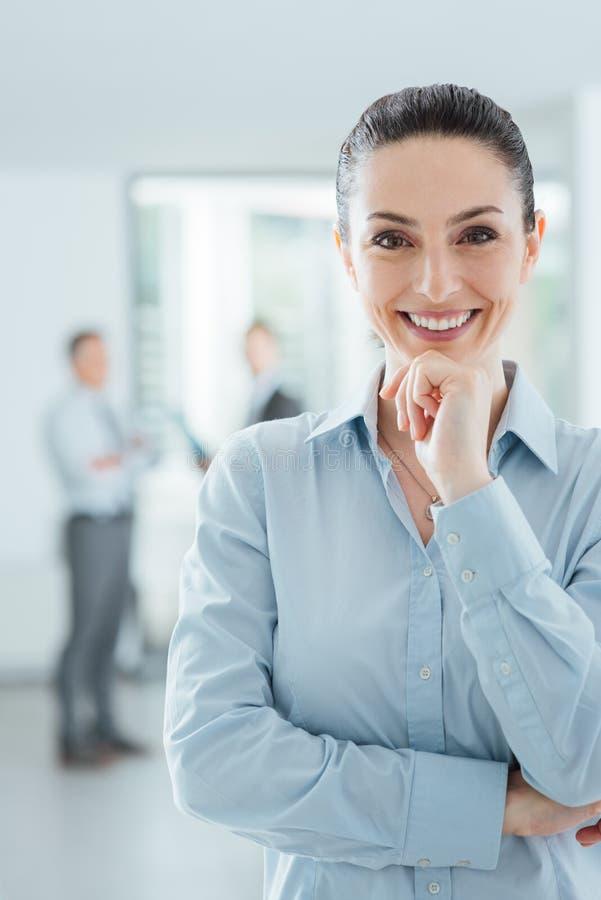 Säker affärskvinna i posera för kontor arkivbilder
