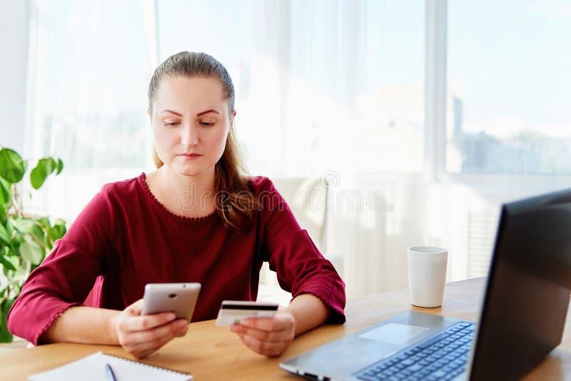 Säker affärskvinna som betalar med kreditkorten på det hemmastadda kontoret för smart telefon, kopieringsutrymme Teknologi bankrö royaltyfri bild