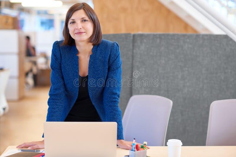 Säker affärskvinna som ler, medan stå på hennes skrivbord arkivfoto
