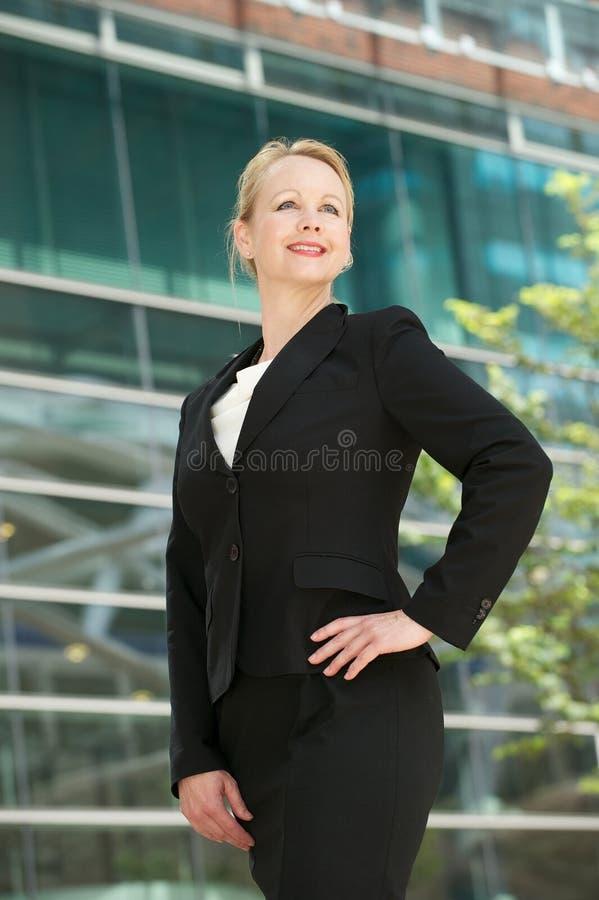 Säker affärskvinna som ler utanför kontorsbu arkivbild