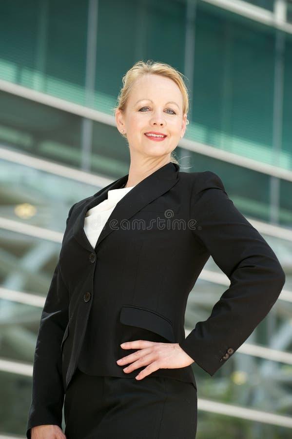 Säker affärskvinna som ler utanför kontorsbui royaltyfria bilder