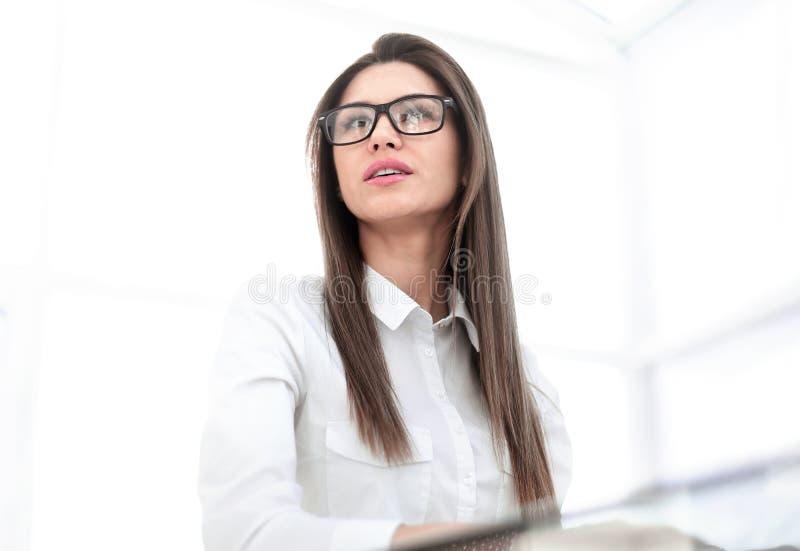 Säker affärskvinna som sitter på kontorsskrivbordet royaltyfri fotografi