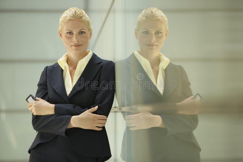Säker affärskvinnaLeaning Against Glass delning royaltyfria bilder