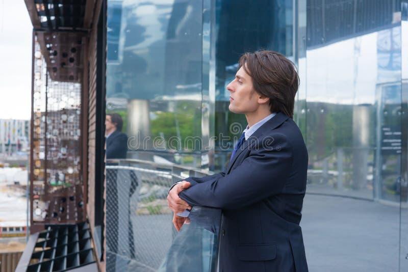 Säker affärsman framme av modern kontorsbyggnad Packa ihop och finansmarknadbegrepp royaltyfri bild