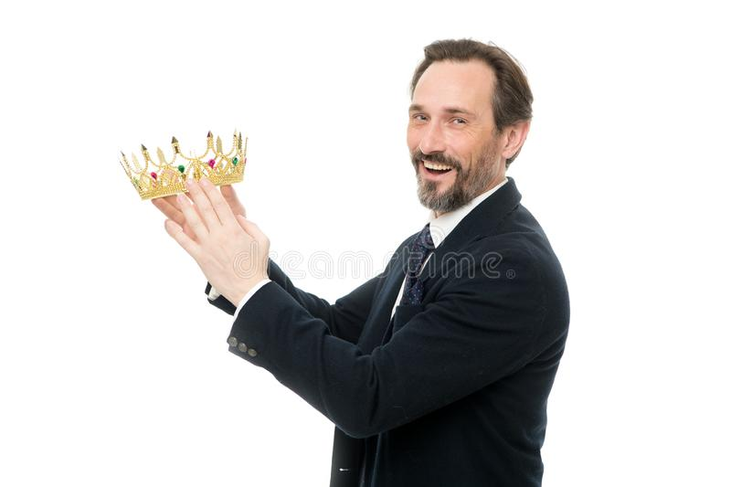 Säker affärsman i kronaanseende som isoleras på grå färger med hans korsade armar Mogen affärsmaninnehavkrona Hög man som förestä royaltyfri fotografi