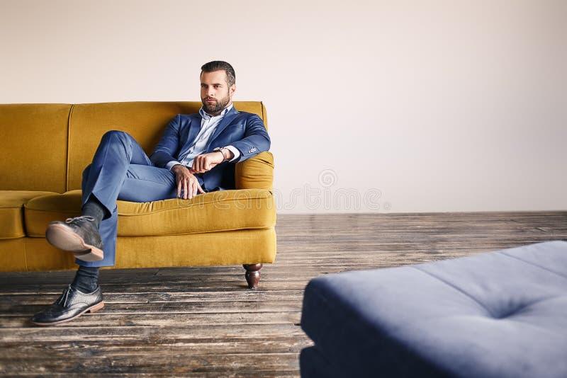 säker affärsman Kopplar av den iklädda trendiga dräkten för den unga och attraktiva skäggiga mannen på soffan på kontoret royaltyfri foto