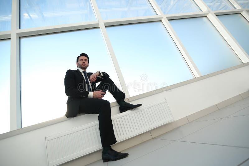 Säker affärsman med ett smartphonesammanträde i kontorshallet royaltyfri foto