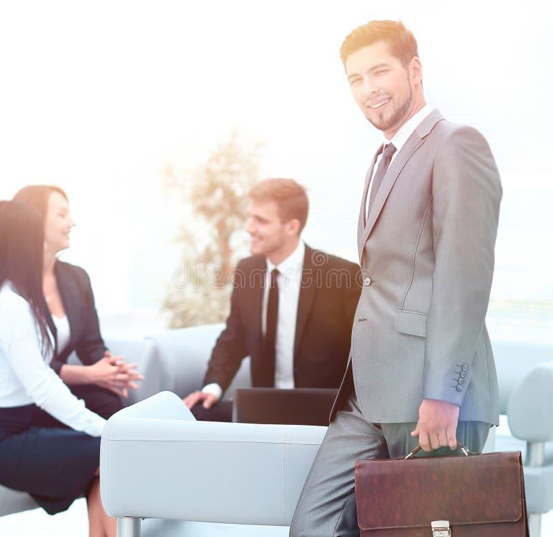 Säker affärsman med portföljanseende i lobbyen av kontoret arkivbild