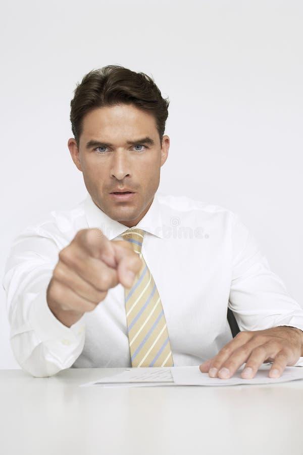 Säker affärsman Pointing While Sitting på skrivbordet arkivbild
