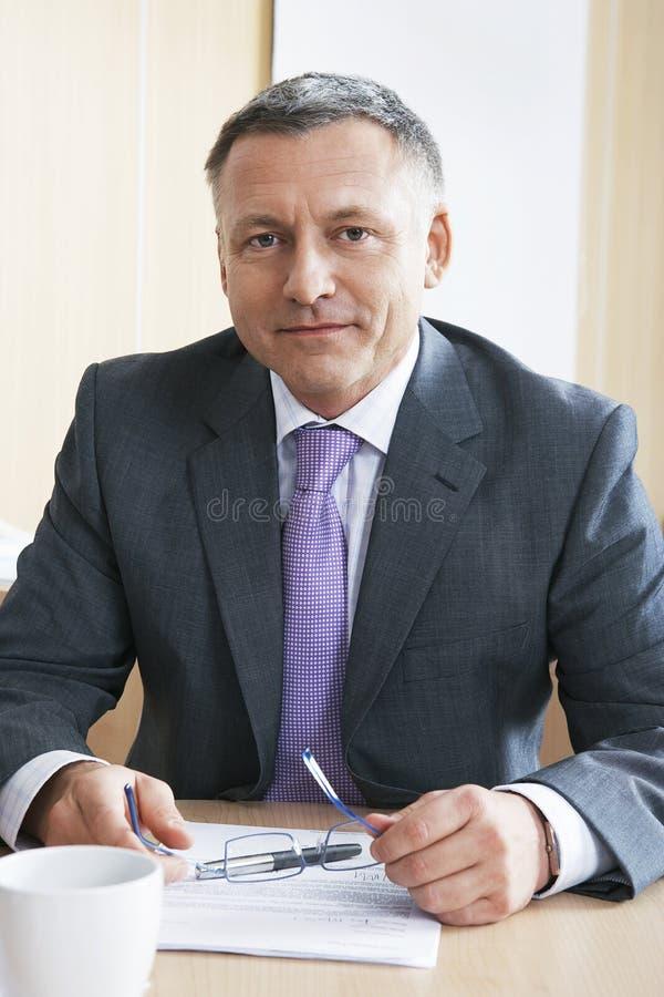 Säker affärsman Sitting At Desk fotografering för bildbyråer