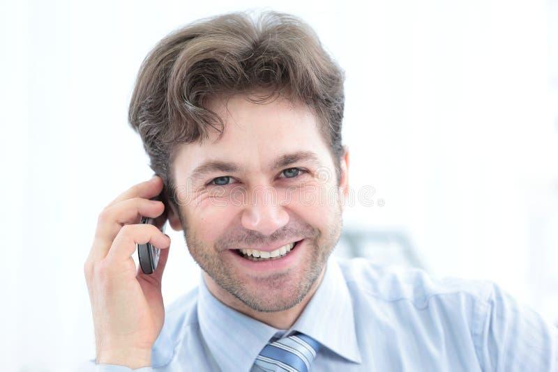 Säker affärsman som talar på telefonen och ler på kameran arkivfoton