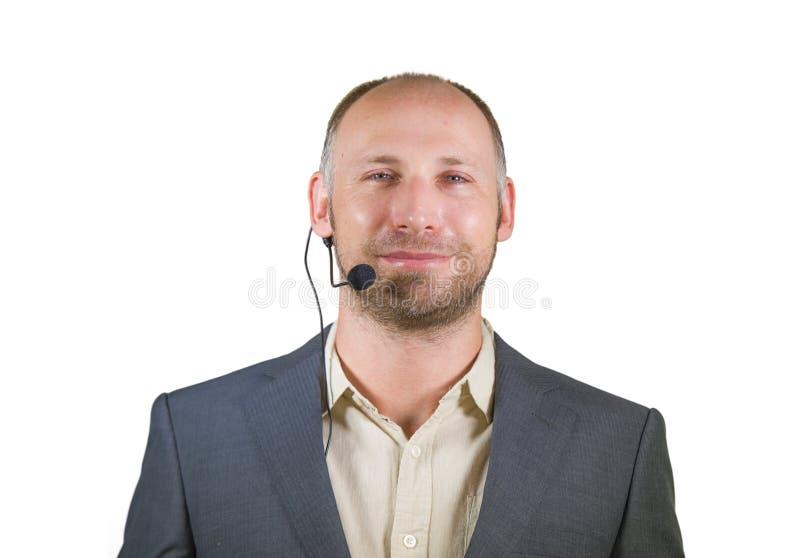 Säker affärsmanhögtalare med hörlurar med mikrofon som ger sig arbeta som privatlärare åt konferensutbildning för att le för affä royaltyfri bild