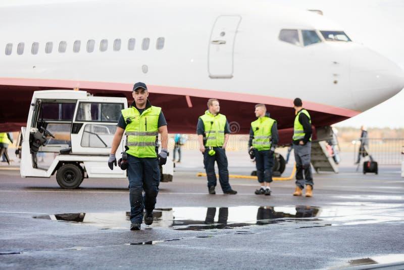Säker arbetare, i att gå medan kollegor som står på våt körning arkivfoto
