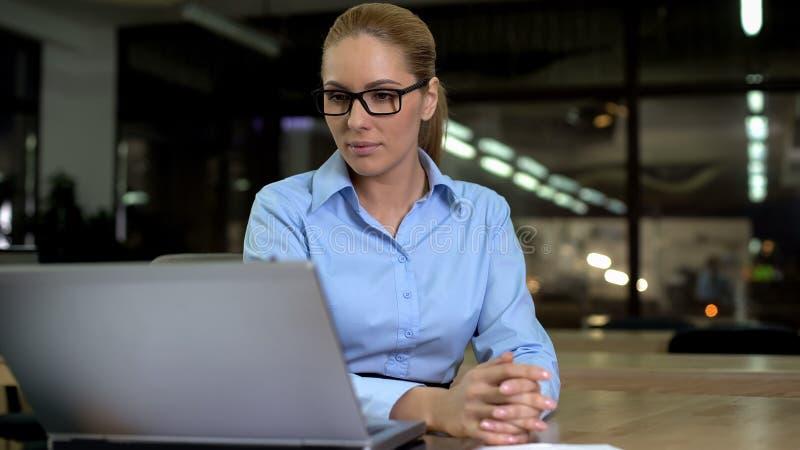 Säker arbetsgivare som studerar information på bärbara datorn, lyckat kvinnligt framstickande arkivbild