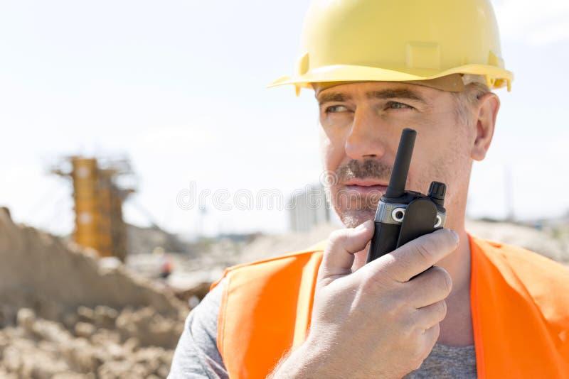 Säker arbetsledare som använder walkie-talkie på konstruktionsplatsen arkivfoton