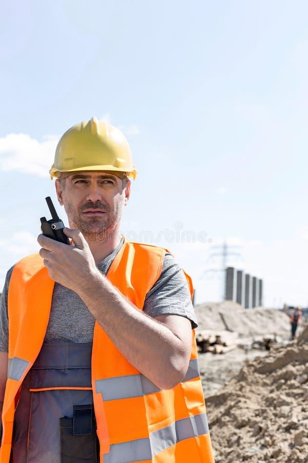 Säker arbetsledare som använder walkie-talkie på konstruktionsplatsen mot himmel fotografering för bildbyråer