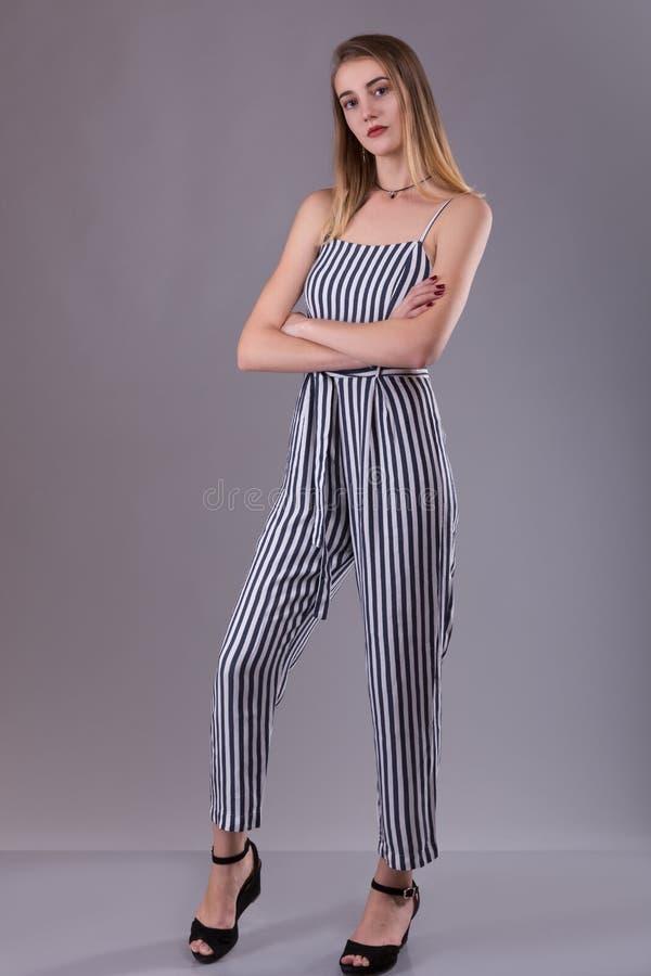 Säker attraktiv spenslig ung kvinna som bär randigt total- anseende med vikta armar som hänsynsfullt över ser på kameran arkivbild