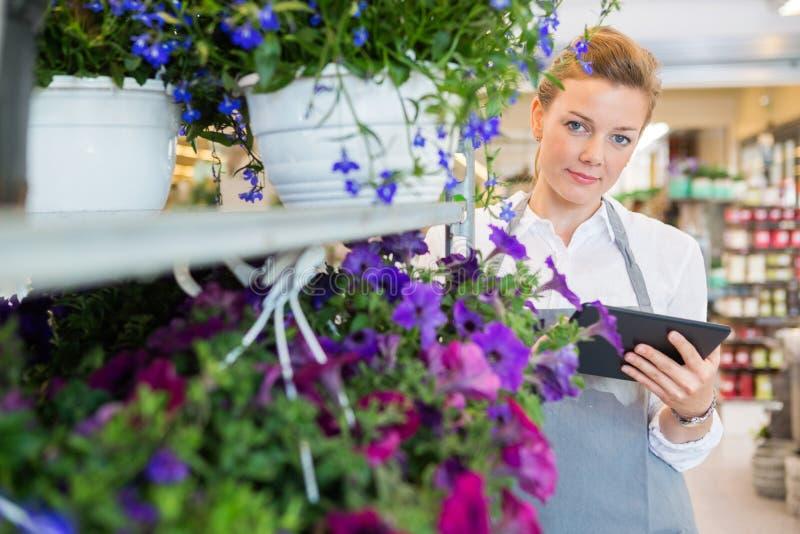 Säker blomsterhandlare Holding Digital Tablet, medan stå vid Flowe royaltyfri foto