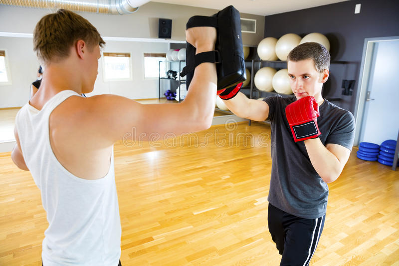 Säker boxare som stansar påsen som rymms av instruktören In Gym royaltyfria bilder