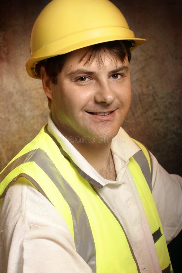 Säker byggmästare, i att le för arbetskläder royaltyfri bild
