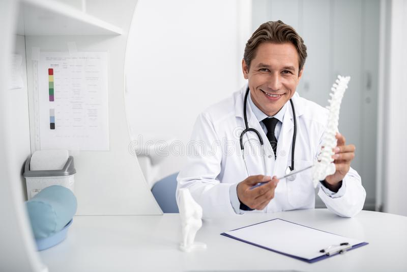 Säker doktor som ler och visar den ryggrads- modellen arkivbilder