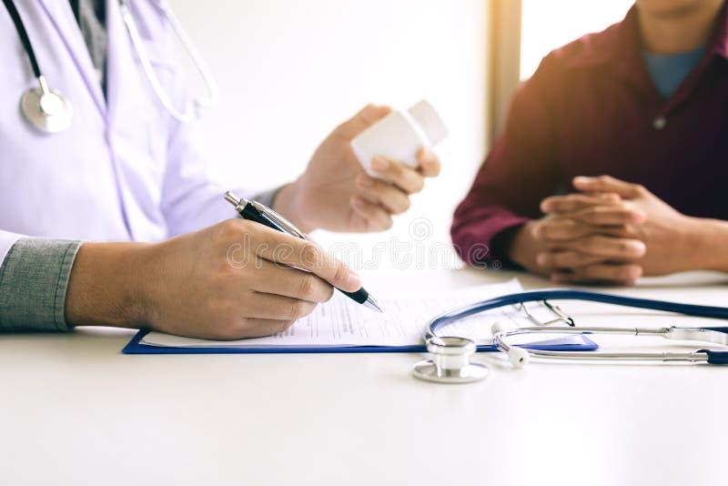 Säker doktorsman som rymmer en pillerflaska och skriver tal stund royaltyfria bilder