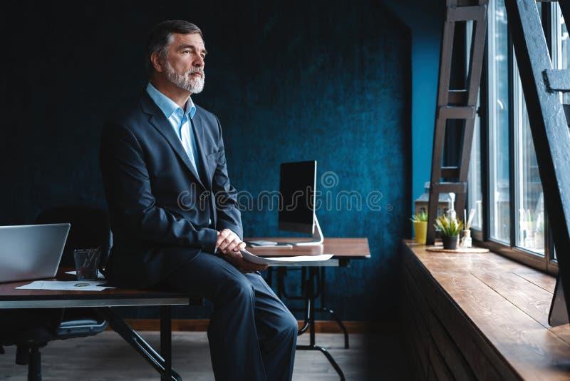 Säker eftertänksam man för mogen affär i modernt kontor arkivfoto