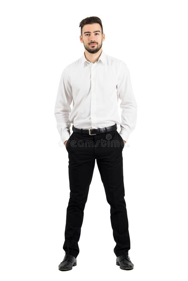 Säker elegant affärsman med händer i fack som ser kameran royaltyfri foto
