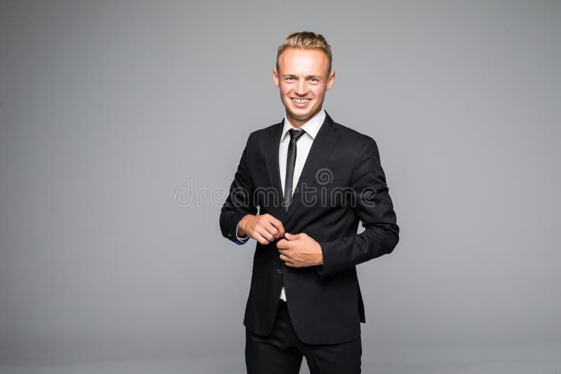 Säker elegant stilig ung man som framme står av en grå bakgrund i en studio som bär en trevlig dräkt arkivfoton