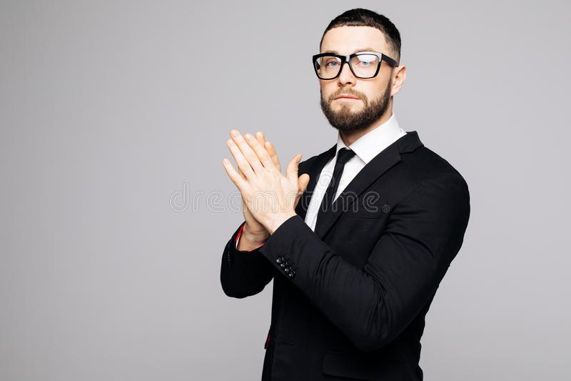 Säker elegant stilig ung man som framme står av en grå bakgrund i en studio som bär en trevlig dräkt arkivfoto