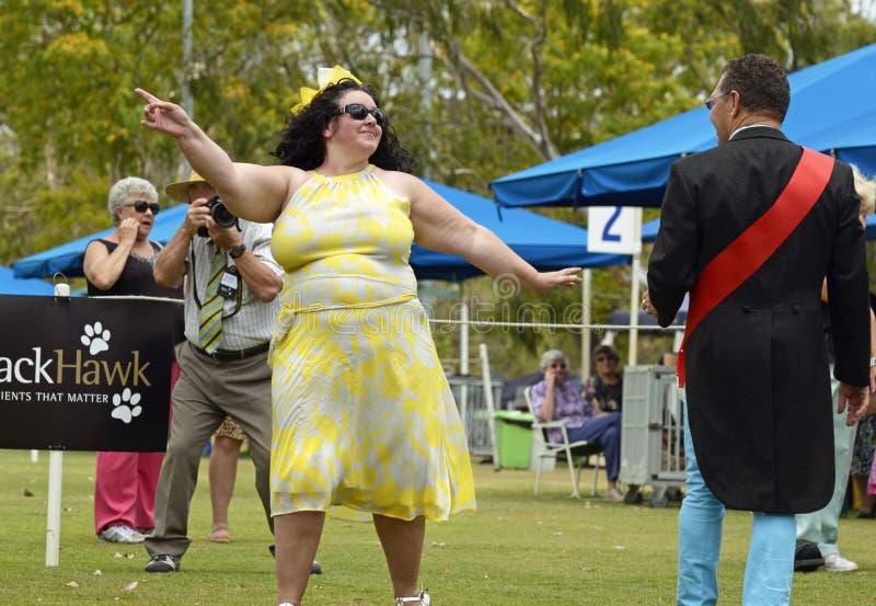 Säker, flamboyant, rolig lycklig plus-format kvinna som modellerar på hundshowen royaltyfri bild
