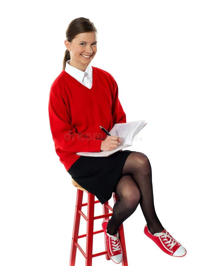 Säker flicka som gör hennes läxa arkivfoto
