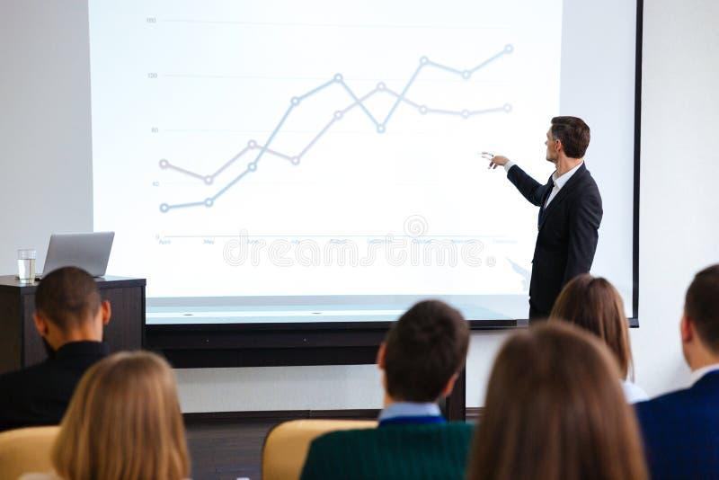 Säker högtalare som ger offentlig presentation genom att använda projektorn royaltyfria foton