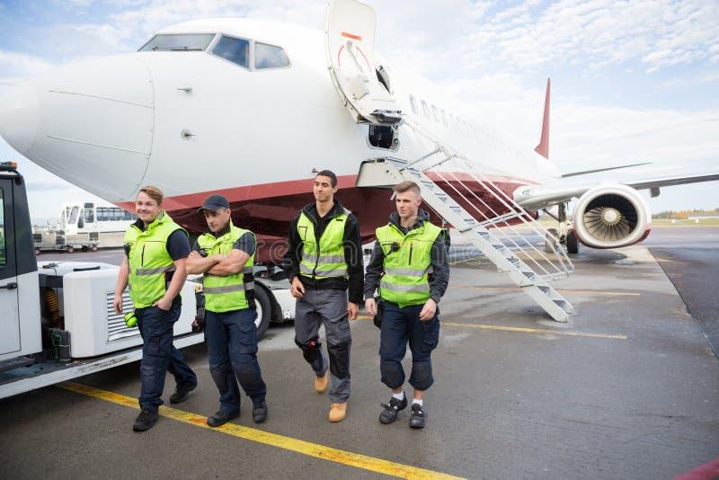 Säker jordbesättning som går mot flygplanet fotografering för bildbyråer