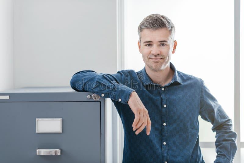 Säker kontorsarbetare som ler och lutar på dokumentskåpet royaltyfri bild