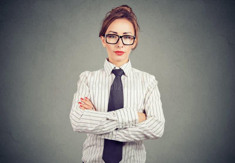 Säker kvinna i formell dräkt och glasögon som rymmer armar korsade och ser kameran royaltyfri bild