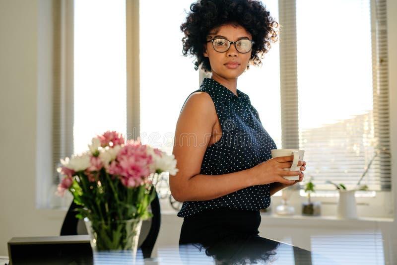 Säker kvinna i regeringsställning med kaffe royaltyfri fotografi