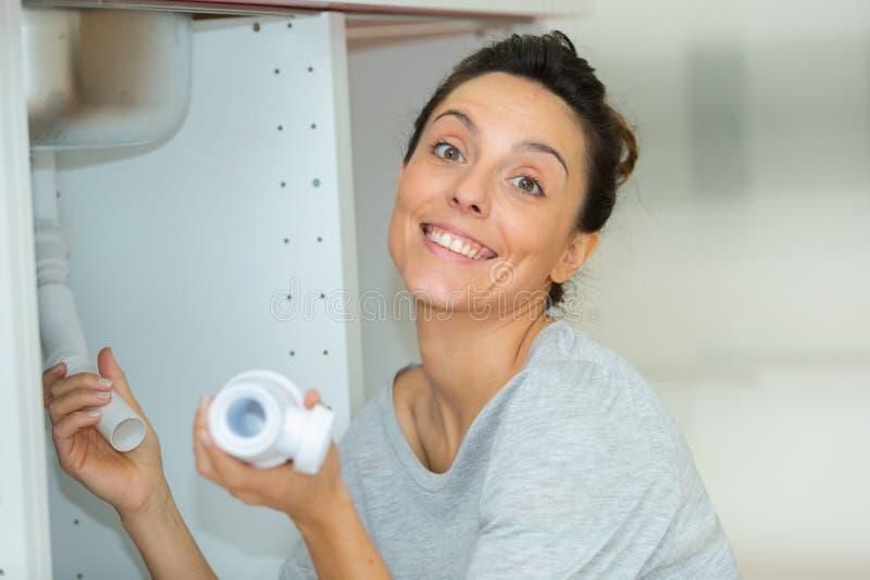 Säker kvinna som hemma reparerar vasken i badrum royaltyfri fotografi