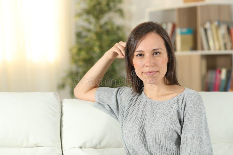 Säker kvinna som hemma ser kameran på en soffa arkivbilder