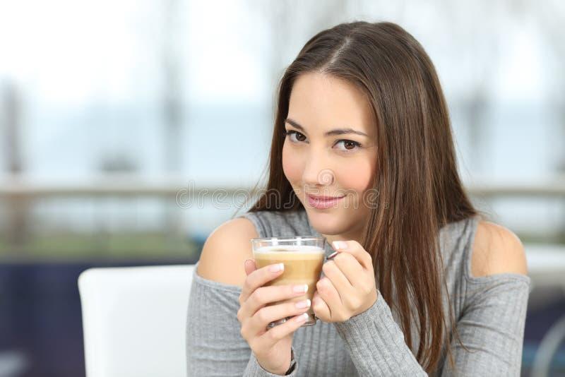 Säker kvinna som poserar rymma en kaffekopp royaltyfri foto