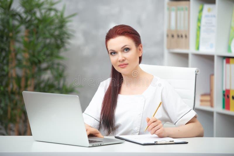 Säker kvinnadoktor som sitter på tabellen i hennes kontor och arbeten på datoren vart begreppshanden har den sena pillen f?r sjuk royaltyfri foto