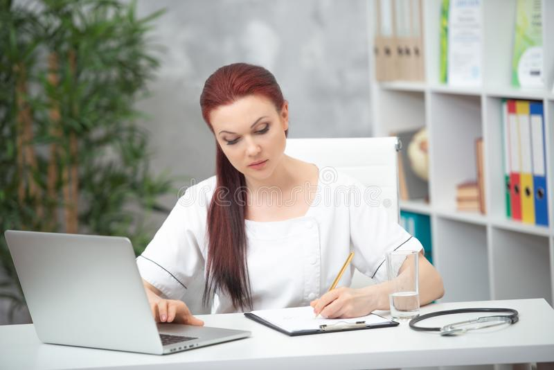 Säker kvinnadoktor som sitter på tabellen i hennes kontor och arbeten på datoren vart begreppshanden har den sena pillen f?r sjuk fotografering för bildbyråer