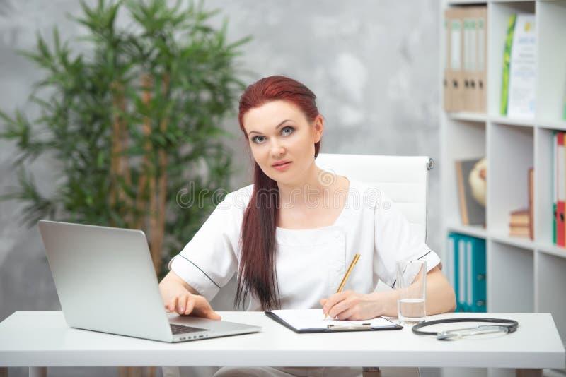 Säker kvinnadoktor som sitter på tabellen i hennes kontor och arbeten på datoren vart begreppshanden har den sena pillen f?r sjuk arkivbilder
