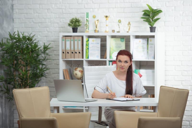 Säker kvinnadoktor som sitter på tabellen i hennes kontor och ler på kameran vart begreppshanden har den sena pillen f?r sjukv?rd royaltyfri bild
